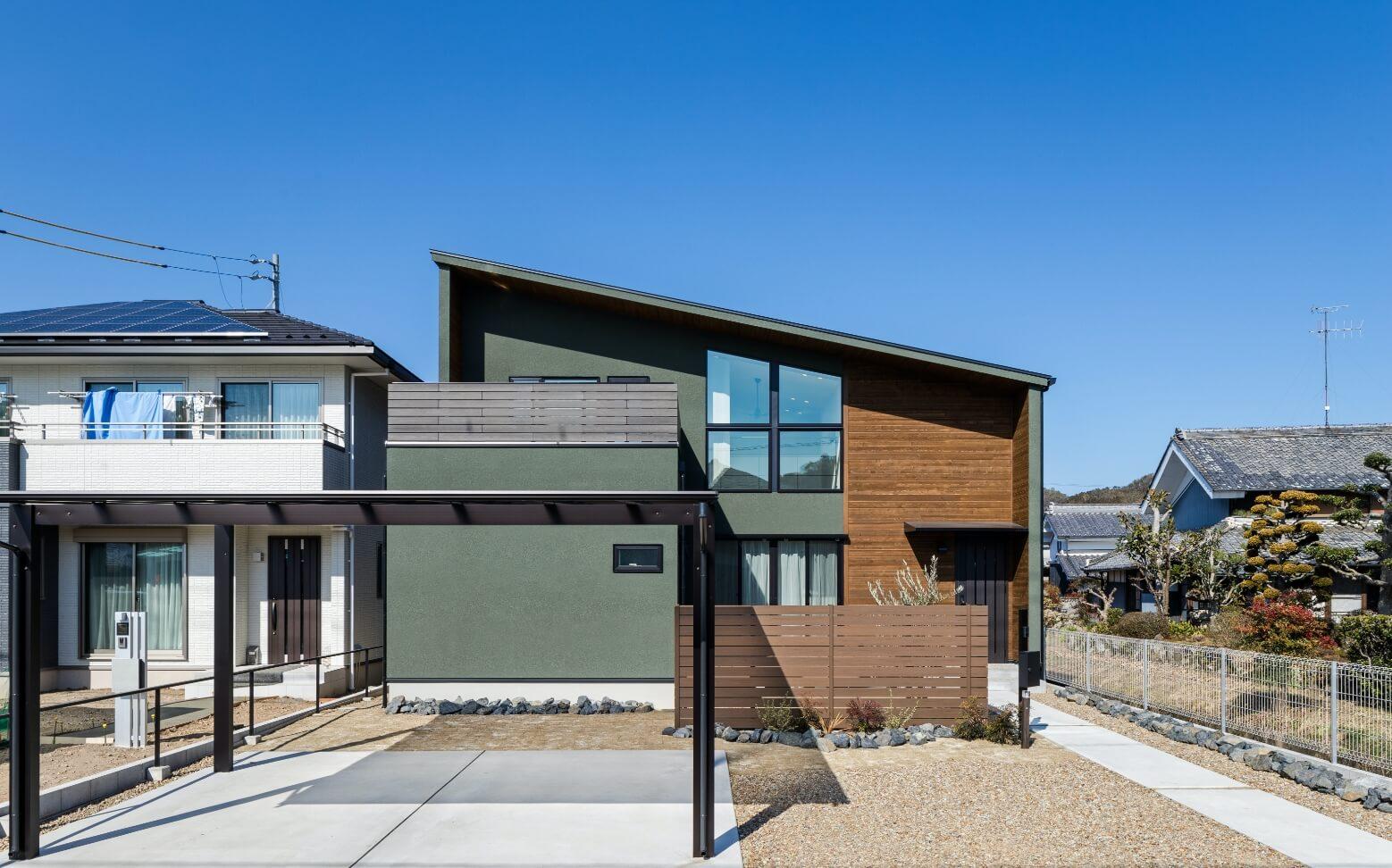 ダークグリーンの塗り壁に、天然木のサイディングが高級感のある森住建住宅の外観